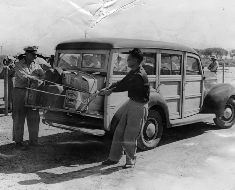 Jap evacuee police are shown here securing baggage on a War Relocation Authority station wagon
