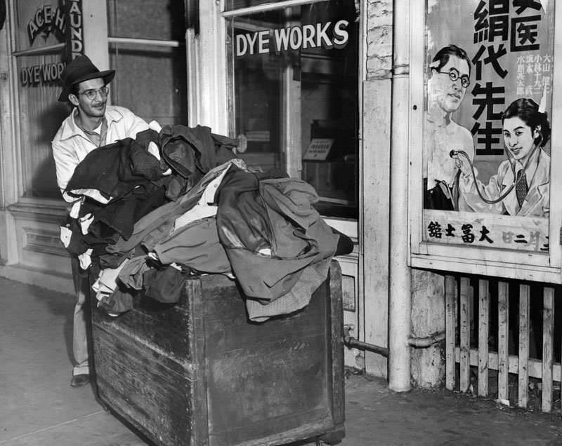 man wheeling a truck load of clothing into cleaning and dye shop