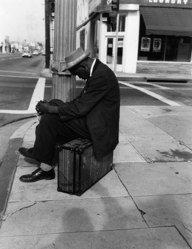man napping on suitcase